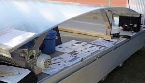 Trailerin päältä teltasta otettu kuva ei tee täyttä oikeutta Ikkuna- ja ovi-parin uudelle kaarevalle harjailmanvaihdolle. Iisalmessa koottu kaariharja poikkeaa selvästi muista harjailmanvaihtoon tehdyistä tuotteista. Umpinainen kaari estää veden valumisen ruokintapöydälle. Sivuilla olevat luukut voidaan avata ja sulkea sähkömoottorin voimin tai veivaamalla. Verkot estävät lintujen pääsyn sisälle. Harja toimii myös tulipalon sattuessa, eikä erillistä savunpoistoa tarvita. Hälytyksen tullessa automatiikka avaa luukut. Yritys on laajentanut navetoihin tarjolla olevaa tuotepalettiaan, ja lisää on luvassa syksyllä. www.iopari.fi